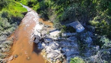 Caminhão cai de ponte e derruba cal em rio; motorista ficou gravemente ferido
